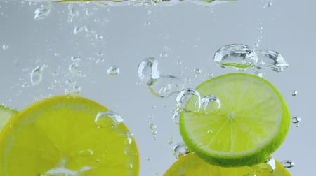 calcário : limes and oranges dropped in water Stock Footage