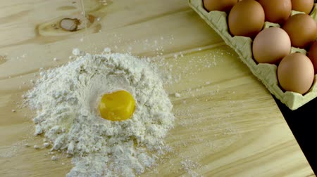 мучной : egg dropping into flour in slow motion Стоковые видеозаписи