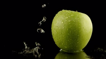 zöldségek : water splashing over green apple in slow motion Stock mozgókép