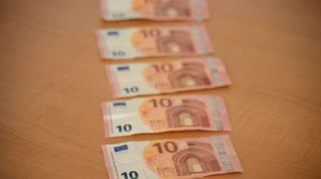 This is footage of ten euro bills laying on a wooden table as the camera pans over them and gets into focus.