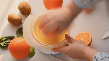 This is video of oranges cut in halves and squeezed into a fresh OJ or orange juice.