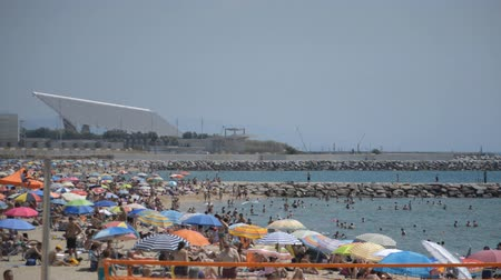 This is footage of a very crowded beach in Spain during high season of beach and sea. The summer in Spain is highly touristic. Стоковые видеозаписи