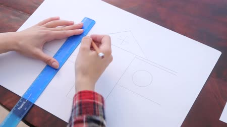 borracha : Girl draws some lines by pencil on paper using a ruler Stock Footage