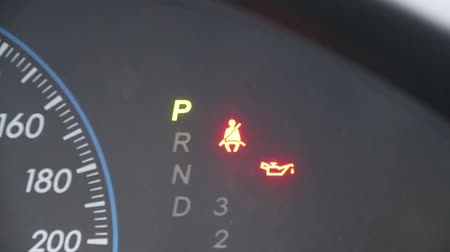 tachometer : Blinking lights of seat belt symbol with numbers that act gear on parking, and lubricant on the dial of car. Stock Footage
