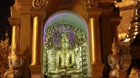 mianmar : Night shot of stucco buddha statue decorated in golden be enshrined inside the arch at Shwedagon Pagoda, Yangon Myanmar.