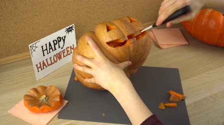 сквош : Womens hands carve the face of a pumpkin for Halloween with a knife