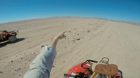 cabo san lucas : driving the ATV in the desert. clean blue sky. people in shawls. only sand, rocks and sky. extremal activity. rest and vacation. tropical resort.