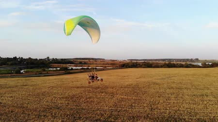 harvesting : flight of a motor-paraglider over the field against the lake