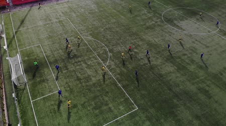 на камеру : Aerial football match play. Aerial shot Two teams playing ball in football outdoors, top view. Football game outdoors, green field with markings, players running around with a ball. GOAL Стоковые видеозаписи