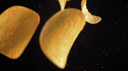 продукты : Potato chips flying up on black background. The view from the top. Pringles. Lays