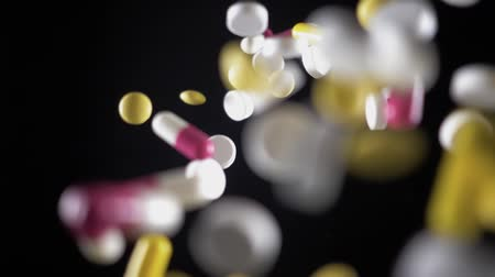 dispanser : a variety of pills fly up and fall. The view from the top. Slow motion