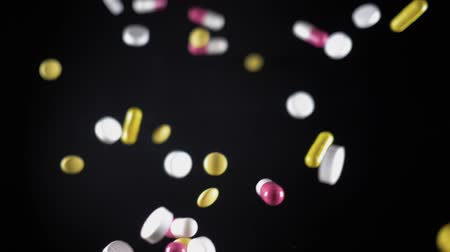 složený : a variety of pills fly up and fall. The view from the top. Slow motion