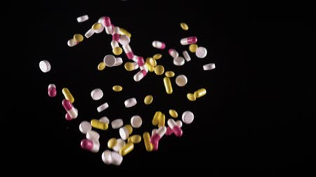 dispensary : a variety of pills fly up and fall. Side view. Slow motion