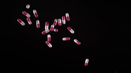 dispensary : a white-pink of pills fly up and fall. Side view. Slow motion Stock Footage