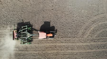 plough land : Orange tractor plows the field. Aerial view.