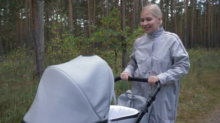goes : a young pretty mother goes with a stroller in the Park and communicates with the baby
