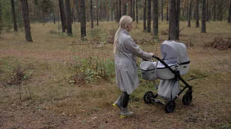 užitečný : Young cute mom walking in the Park with a stroller. listening to music and dancing