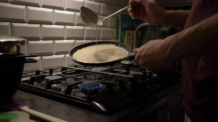навес : a man pours the dough for pancakes in the pan. Man cooking pancakes