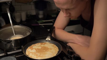 навес : Man cooking pancakes at night. A man watches how a pancake is cooked in a frying pan. Стоковые видеозаписи