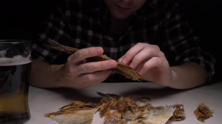 рыболовство : close-up. Male hands clean the salted dried fish in night. 4K