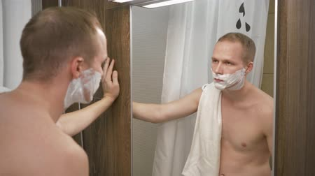 contato com os olhos : man shaves his face. handsome man shaving in the bathroom. 4k