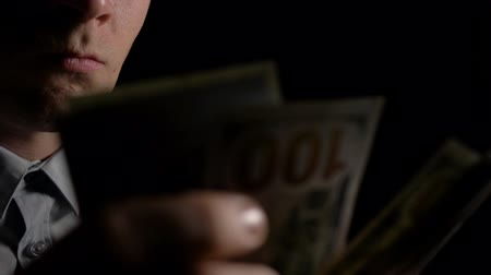 prémie : A man in the dark counting dollars. The man counts the dollars. Money in mens hands. Unexpected win. The fee for the work done.He shakes with money. Close up. Slow motion. 4K