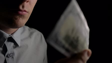 Вениамин : A man checks dollars for authenticity. A man sniffs dollars. Clous up. 4k slow motion