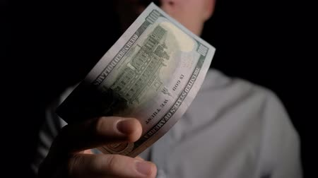 lots of money : A man checks dollars for authenticity. A man sniffs dollars. Clous up. 4k slow motion