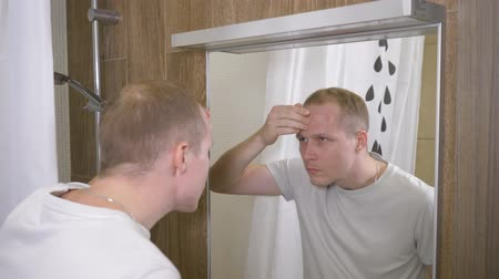 hidratáció : A young handsome man. The man saw acne on his forehead in the mirror. 4k slow motion Stock mozgókép