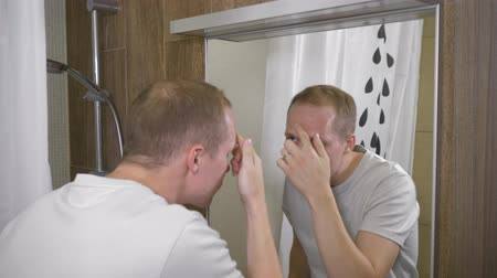 uklidňující : A young handsome man. The man saw acne on his forehead in the mirror. A man covers acne with a concealer. 4k slow motion Dostupné videozáznamy