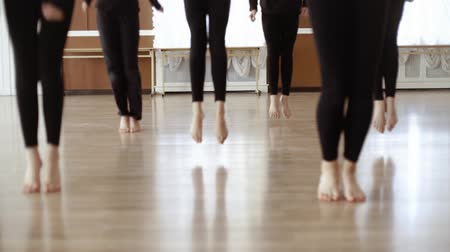 posição : Girls to dance class. Girls in black clothes dancing in the dance hall. Girls warm up before dancing. Close-up legs. Slow motion Vídeos