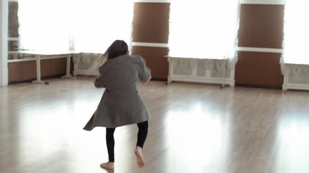 колготки : A little girl for a dance class. Girl in a gray coat dancing in the dance hall. Slow motion Стоковые видеозаписи