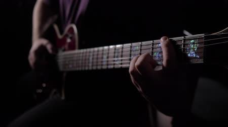 banquinho : man is sitting and playing the guitar in a dark room. Close up. 4K