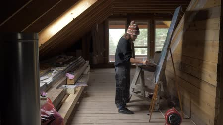 raso : Man artist paints a picture of oil paints in the attic. 4K Vídeos