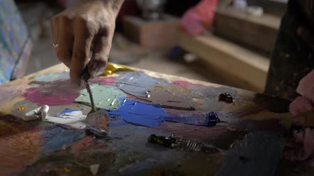 expressionism : artist palette knife mix color oil painting on palette is holding in his hand close up. In workshop. 4K