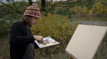 expressionism : Artists palette knife oil painting mix colors on the palette holding a close-up. Artist on the street by the river. 4K Stock Footage