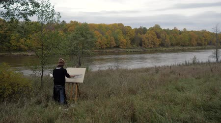 ami : A young and creative artist paints a picture on a canvas in an open air, a man paints a brush on the canvas, which stands on an easel in the nature by the river. Autumn. 4K