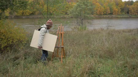 művésziesség : The artist sets an easel in nature on the banks of the river. 4K