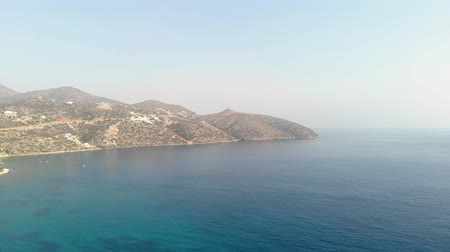 sedir : Greek island coast with clear blue sea, rocks above the water, on a summer day. Aerial view. 4K.