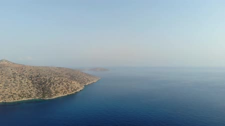waters : Greek island coast with clear blue sea, rocks above the water, on a summer day. Aerial view. 4K.