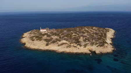 magánélet : Copter fly around the small island with old house surrounded by sea space. Island with one house. Loneliness. Aerial view. 4K