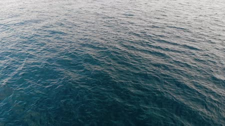 вниз : Top-down view of the sea waves. Sea ripples. Aerial view. The background of the sea. The texture of the water. Calm sea shot from above. 4K