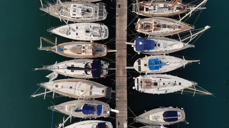 kypr : Aerial view of the Marina. Parking boats from a height. Port with yachts. City pier. Top view of the Marina. Yacht on the pier view from the top. Flying over the yacht. Aerial view. 4K