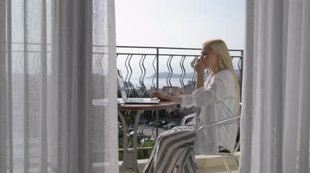 terra : Working with a laptop. Beautiful elegant girl with a computer on the terrace overlooking on the Bay. 4K. Stock Footage