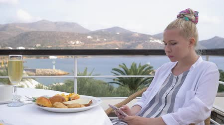 УВР : Beautiful elegant girl having breakfast at outdoor cafe with amazing view on the see. Woman use the telephone on luxury hotel terrace with sea view at resort restaurant. 4K