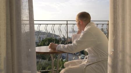балкон : A young man in a white robe drinking coffee on the terrace. 4K Стоковые видеозаписи