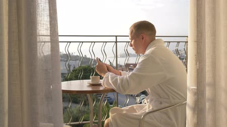 odeslat : A young man in a white robe drinking coffee on the terrace. 4K Dostupné videozáznamy