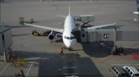 minibus : Aircraft which stands near airport terminal. The plane stands at the ramp. The view from the terminal. 4K. Stock Footage