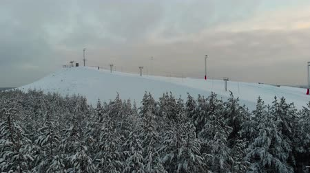 домик : The camera flies over the forest towards the ski resort. Aerial view winter extreme on ski lodge. The top of the ski resort. Mountain top. 4K