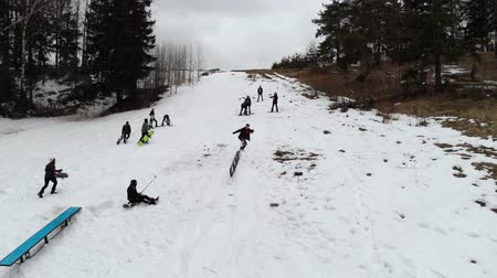 chairlift : Snowboarding jibbing. Snowboarders perform tricks on the figures of jibbing. Aerial view. A snowboarder rides through a metal rail. The fall of snowboarder. 4K